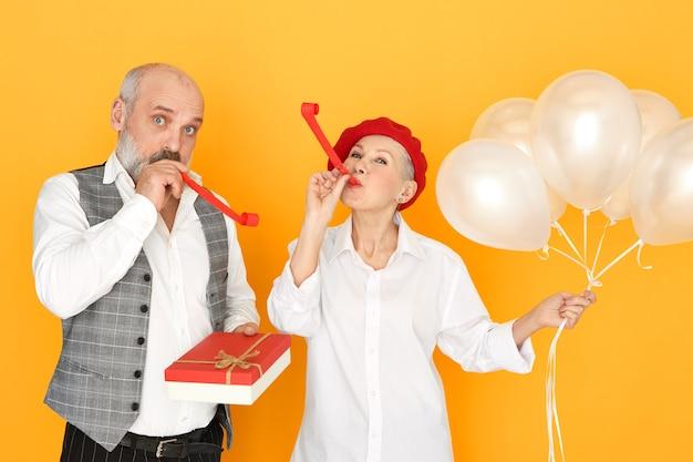 Atrakcyjna kobieta w średnim wieku pozowanie na białym tle z balonami helem z brodaty starszy mężczyzna trzyma pudełko czekolady, dmuchanie gwizdkami