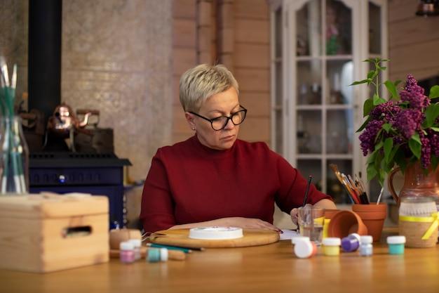 Atrakcyjna kobieta w średnim wieku przyciąga do przytulnego wiejskiego domu z kominkiem