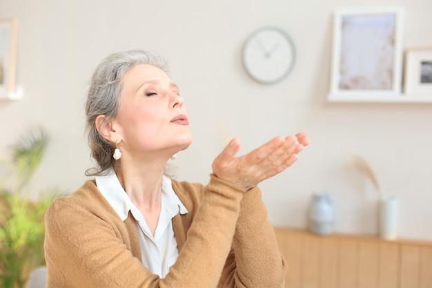 Atrakcyjna kobieta w średnim wieku relaksuje w kanapie w domu.