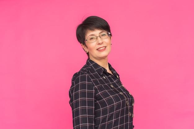 Atrakcyjna kobieta w średnim wieku w okularach na różowym tle