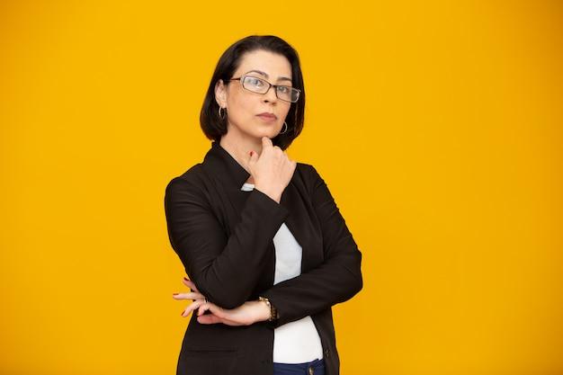 Atrakcyjna kobieta w średnim wieku z okularami i rękami skrzyżowanymi