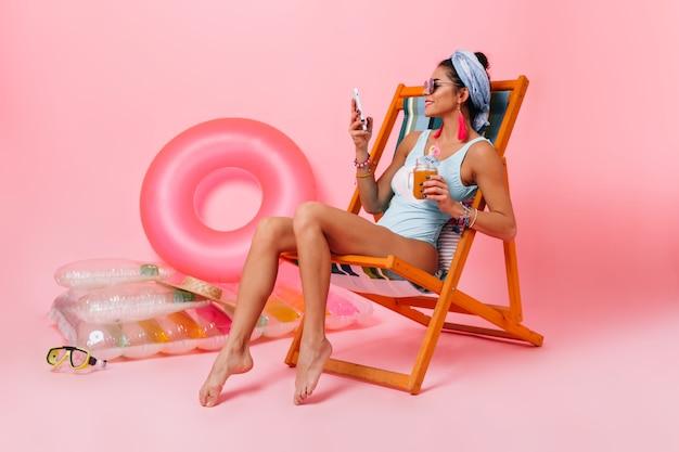 Atrakcyjna kobieta w stroju kąpielowym siedzi w leżaku