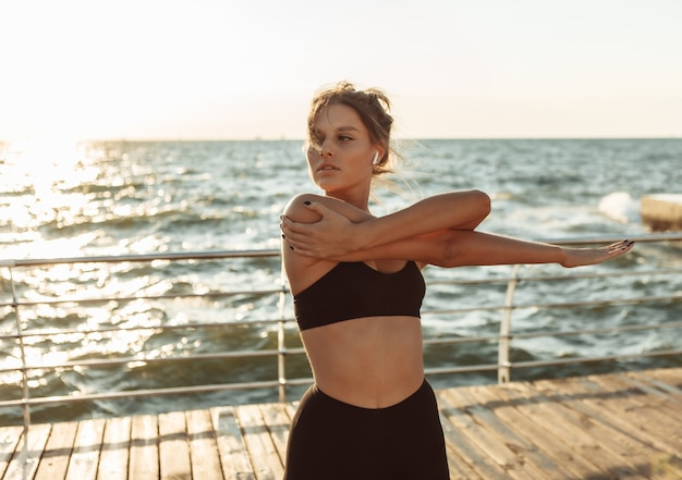 Atrakcyjna kobieta w stroju sportowym robi rozciąganie dłoni przed ćwiczeniami na plaży o wschodzie słońca