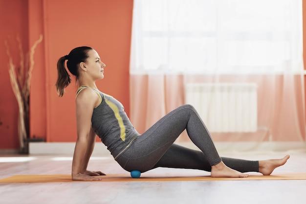 Atrakcyjna kobieta w stroju sportowym, siedząc na macie gimnastycznej, wykonuje rozluźnienie mięśniowo-powięziowe mięśni pośladkowych piłką do masażu