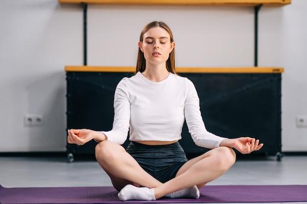 Atrakcyjna kobieta w stroju sportowym siedząca w pozycji lotosu podczas wykonywania jogi w domu