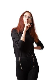 Atrakcyjna kobieta w stylizacji i jasny makijaż w czarnej twater kurtce i spodniach, trzymając palec w ustach w ciszy i patrząc na kamery na białym tle. portret kobiety