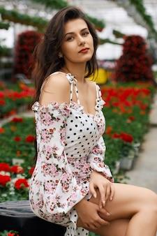 Atrakcyjna kobieta w stylowej sukience pozowanie w oranżerii