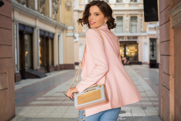 Atrakcyjna kobieta w stylowym stroju spacery po mieście, moda uliczna, trend wiosenno-letni, uśmiechnięty szczęśliwy nastrój, ubrana w różową kurtkę i bluzkę, widok z tyłu, elegancja, wakacje w europie