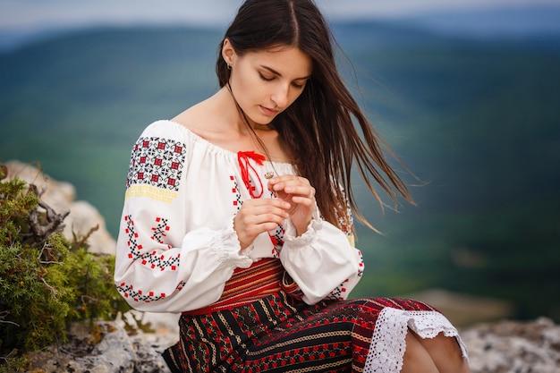 Atrakcyjna kobieta w tradycyjnych strojach rumuńskich na zielonej górze niewyraźne tło. zdjęcie plenerowe. tradycje i różnorodność kulturowa