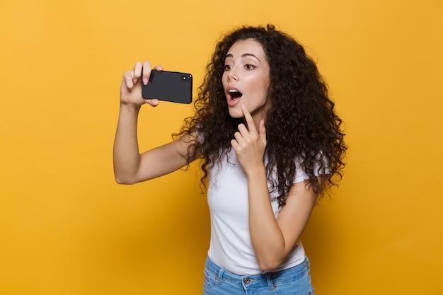 Atrakcyjna kobieta w wieku 20 lat z kręconymi włosami śmiejąca się i robiąca zdjęcie selfie na telefonie komórkowym odizolowanym na żółto