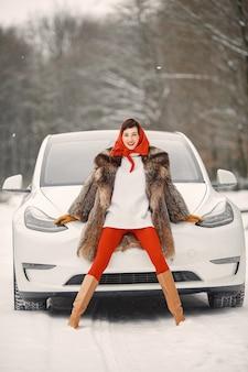 Atrakcyjna kobieta w zimie plenerowym z białym samochodem