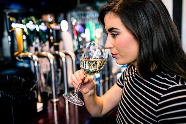 Atrakcyjna kobieta wącha białe wino