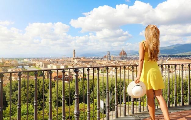 Atrakcyjna kobieta we florencji, kolebce renesansu. pełny widok długości ładnej dziewczyny z panoramicznym widokiem na miasto florencja w toskanii we włoszech.