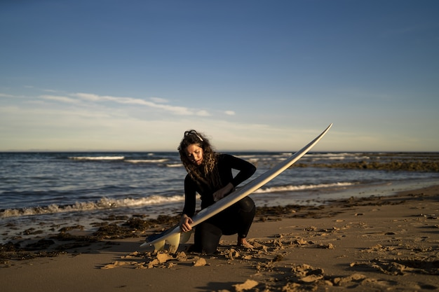 Atrakcyjna kobieta woskowanie jej deska surfingowa na plaży w hiszpanii