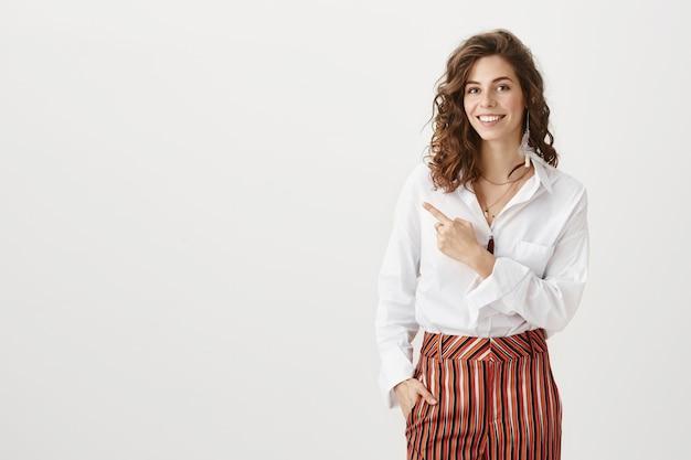 Atrakcyjna kobieta wskazując w lewo w stylowym stroju