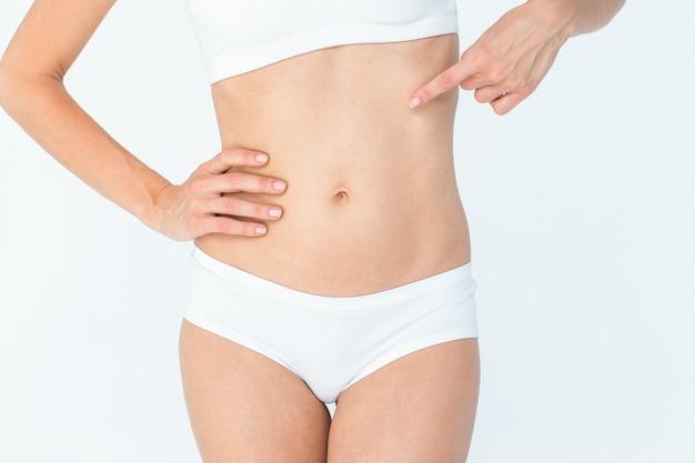 Atrakcyjna kobieta wskazuje jej brzucha