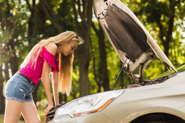 Atrakcyjna kobieta wygląda w otwartej masce samochodu