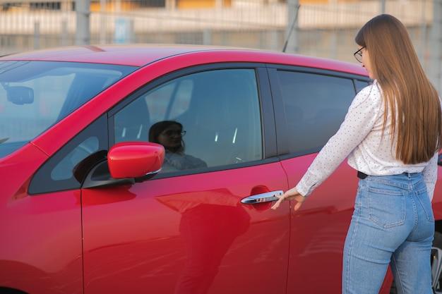 Atrakcyjna kobieta wykorzystująca nowoczesną technologię do odblokowywania drzwi samochodowych. kobieta otwiera drzwi i dostaje w samochodzie. dziewczyna otwiera samochód i siada w środku