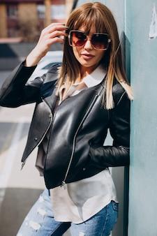Atrakcyjna kobieta z blond włosami pozuje na ulicy