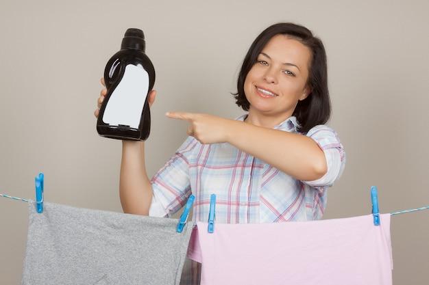 Atrakcyjna kobieta z czarną plastikową butelką detergentu wiszącą wilgotną czystą ściereczką do wyschnięcia na sznurku w pralni na szarym tle