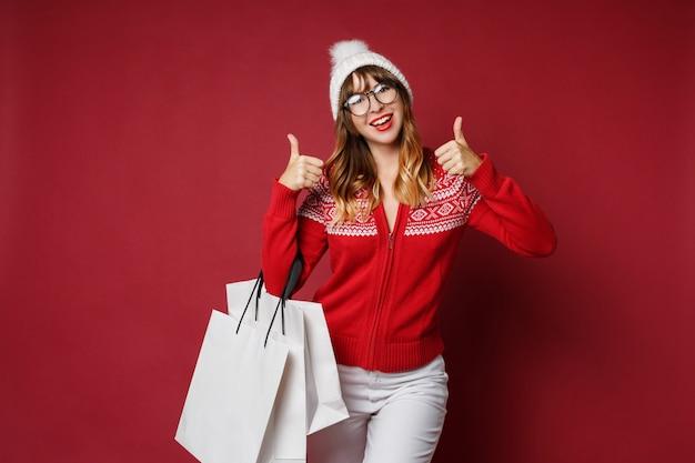 Atrakcyjna kobieta z falistymi włosami stoi z białymi torba na zakupy
