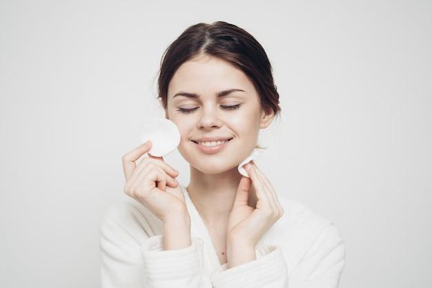 Atrakcyjna kobieta z gąbką iw białym szlafroku
