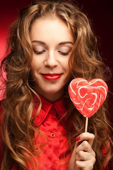 Atrakcyjna kobieta z karmelem serca na czerwonym tle