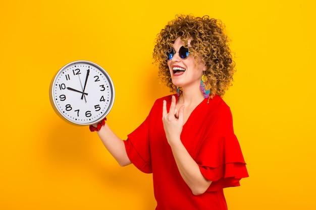 Atrakcyjna kobieta z krótkimi kręconymi włosami z zegarami