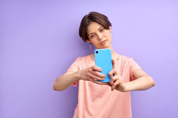 Atrakcyjna kobieta z krótkimi włosami robi zdjęcie telefonem komórkowym, robi selfie z poważną twarzą pozującą iso...