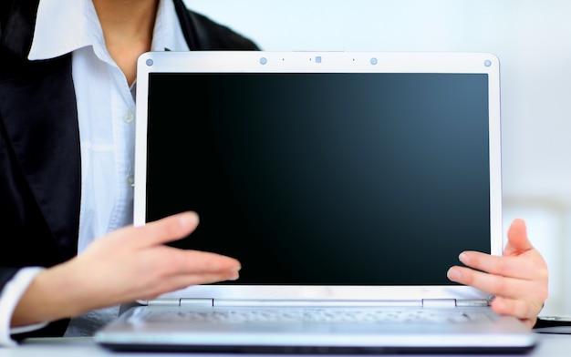 Atrakcyjna kobieta z laptopem w ręce uśmiechając się, w biurze.
