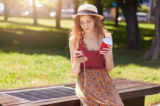 Atrakcyjna kobieta z lisimi włosami ładuje telefon komórkowy na ławce z panelem słonecznym, pije kawę i sprawdza wiadomości e-mail lub pisze wiadomości