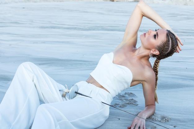 Atrakcyjna kobieta z mieczem w białym stroju totalnym. strzelaj mody na pustyni