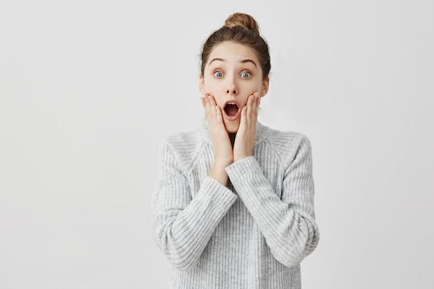 Atrakcyjna kobieta z otwartymi ustami jest zszokowana. studentka chwytająca twarz jest zdumiona wynikiem egzaminu. koncepcja edukacji