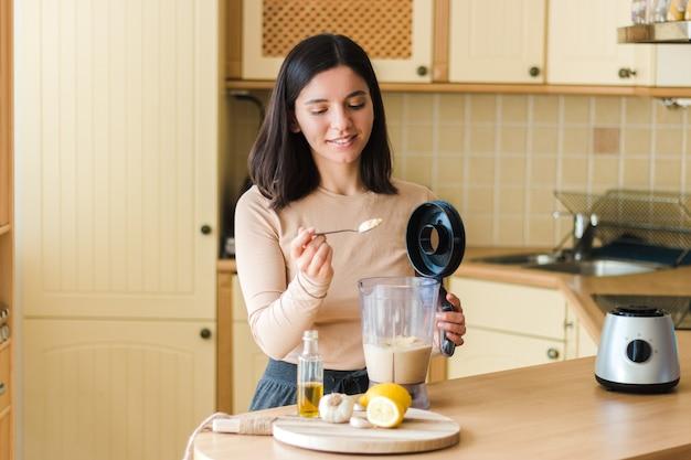 Atrakcyjna kobieta z pięknym uśmiechem w kuchni przygotowuje naturalne wegetariańskie jedzenie domowe hummus z ciecierzycy przepis