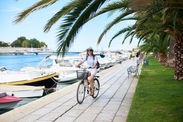 Atrakcyjna kobieta z plecakiem, jazda rowerem wzdłuż kamienistego chodnika z żelazną ławką i palmami