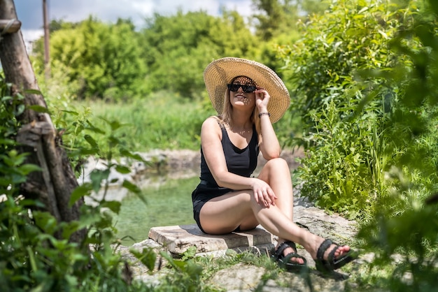 Atrakcyjna kobieta z przyrodą w pobliżu stawu