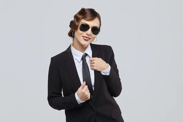 Atrakcyjna kobieta z retro fryzurą i uśmiechem na twarzy. pozuje w męskim garniturze i okularach przeciwsłonecznych
