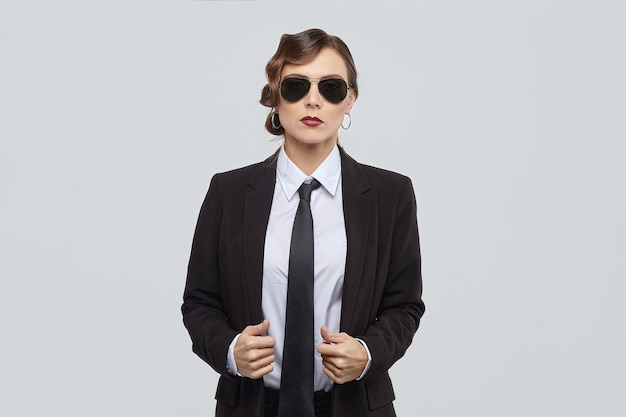 Atrakcyjna kobieta z retro fryzurą pozuje w męskim garniturze i okularach przeciwsłonecznych