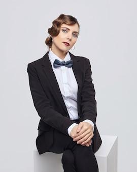 Atrakcyjna kobieta z retro fryzury pozuje w garniturze mężczyzny. sesja zdjęciowa w studio na białym tle