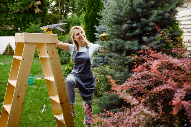 Atrakcyjna kobieta z sekatorami wchodzi po schodach w ogrodzie