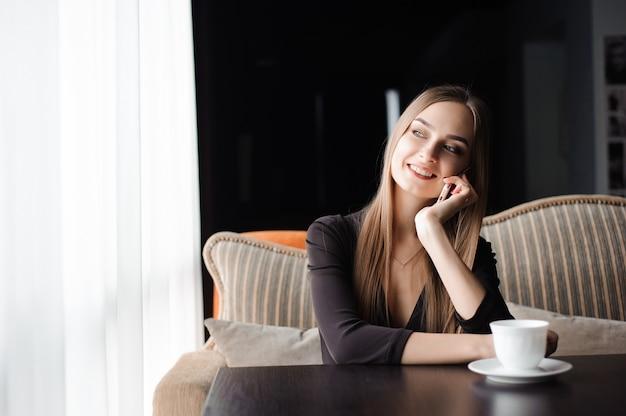 Atrakcyjna kobieta z uroczym uśmiechem po rozmowie z telefonem komórkowym podczas odpoczynku w kawiarni.