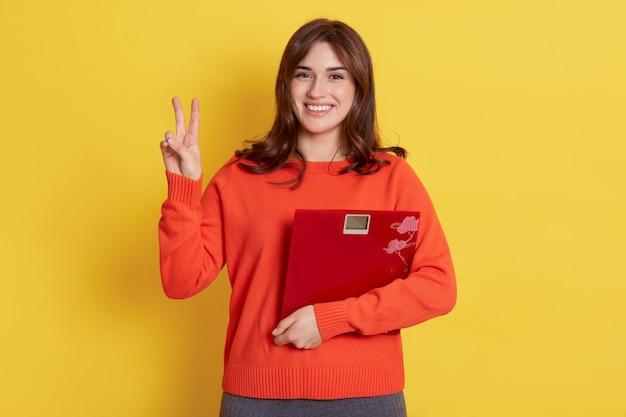 Atrakcyjna kobieta z wagą w rękach wygląda na bardzo szczęśliwą, pokazując znak v