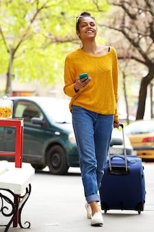 Atrakcyjna kobieta z walizką i telefonem komórkowym na miasto ulicie