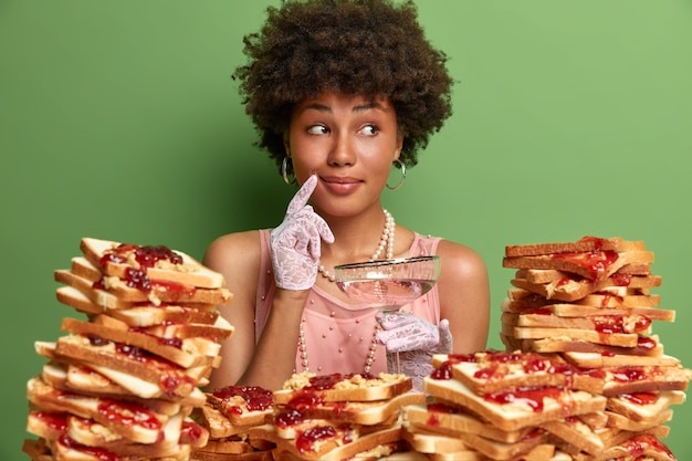 Atrakcyjna kobieta z włosami afro otoczona galaretowatymi kanapkami z masłem orzechowym