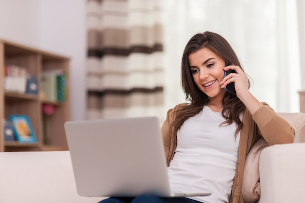 Atrakcyjna kobieta za pomocą laptopa i inteligentnego telefonu w domu