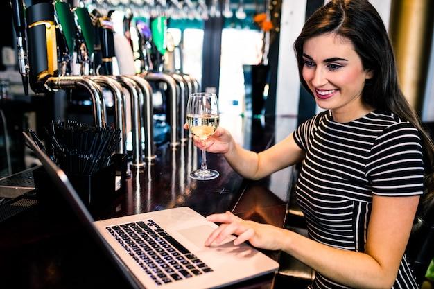 Atrakcyjna kobieta za pomocą laptopa i kieliszek wina w barze