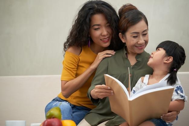 Atrakcyjna kochająca młoda wietnamska kobieta obejmująca starszą matkę podczas czytania książki wnuczce