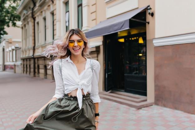 Atrakcyjna, kręcona kobieta ze szczerym uśmiechem bawi się swoją długą spódnicą podczas spaceru ulicą