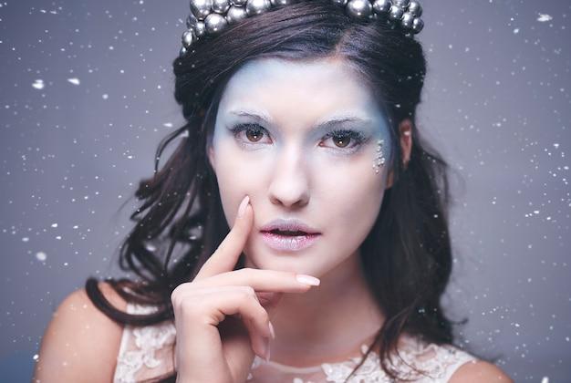 Atrakcyjna królowa śniegu wśród padającego śniegu
