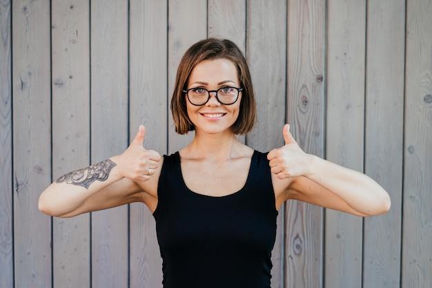 Atrakcyjna krótka z włosami dziewczyna w szkłach ubierał w czarnej koszulki szeroki ono uśmiecha się, pokazuje aprobata gest obiema rękami nad drewnianym ściennym tłem. koncepcja szczęśliwych ludzi.